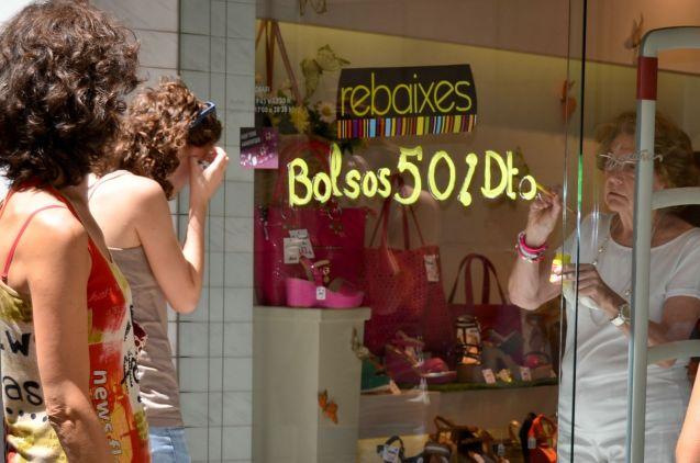 Una comerciante del Eix Comercial publicita las rebajas en su tienda Cecília López