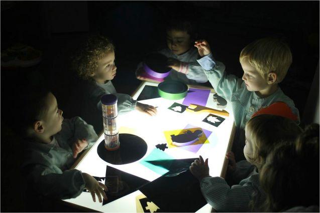 Varios niños descubren el juego de colores que proyecta una caja de luz en las EBM de Lleida. Ajuntament de Lleida